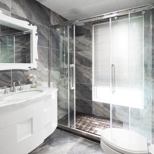 sliding glass shower door in grey bathroom